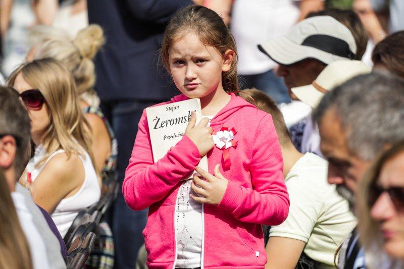 Na zdjęciu dziewczynka trzyma książkę Przedwiośnie.